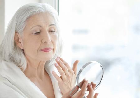 Schöne ältere Frau, die Spiegel hält und zu Hause Gesichtscreme aufträgt