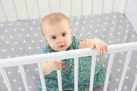 Cute little girl sitting in crib at home