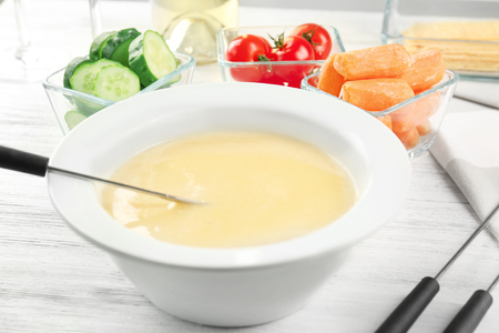 Delicious cheese fondue and vegetables on table Archivio Fotografico