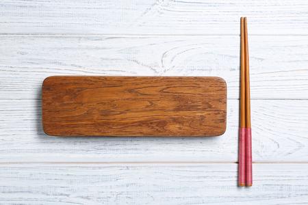 Rectangular wooden board and chopsticks on table Stok Fotoğraf