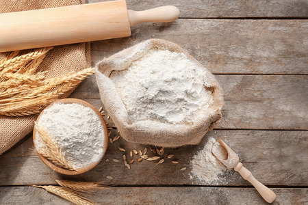 Composition with flour and kitchen utensils on wooden background Foto de archivo