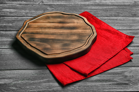 Empty wooden board and napkin on table