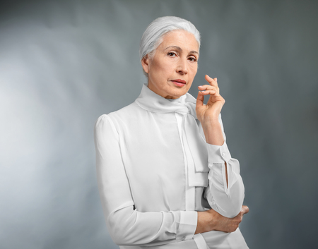 Beautiful elegant elderly woman on gray background