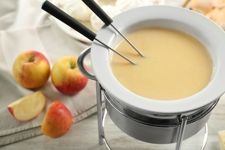 Delicious cheese fondue and apples on table