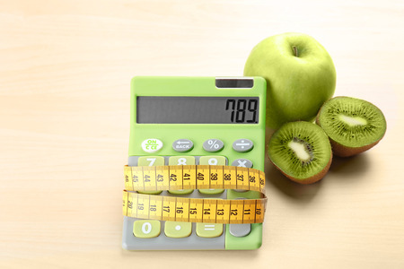 Weight loss concept. Apple, kiwi, calculator and measuring tape on light background