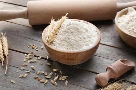 Composizione con farina e utensili da cucina su fondo in legno