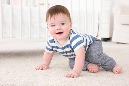 Lindo bebé sentado en el piso cerca de la cuna en casa Foto de archivo