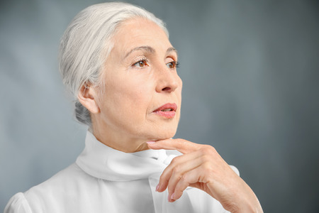 Beautiful elegant elderly woman on gray background Stock fotó - 111206620