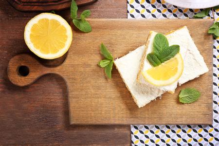 Delicious lemon pie bars on wooden board
