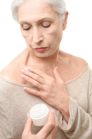 Beautiful elderly woman applying cream onto skin, on white background Stock Photo