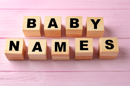 Cubes with words BABY NAMES on color wooden background