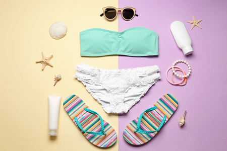Beautiful bikini and beach accessories on color background