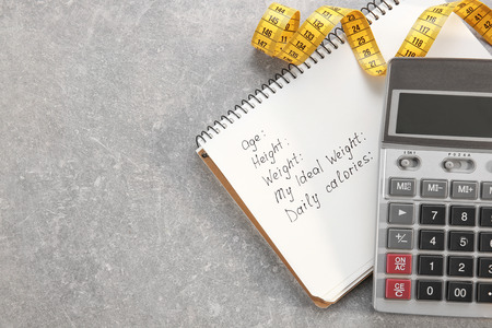 Diet concept. Measuring tape, calculator and notebook on gray background