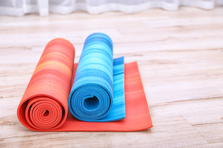 Two yoga mats on wooden floor