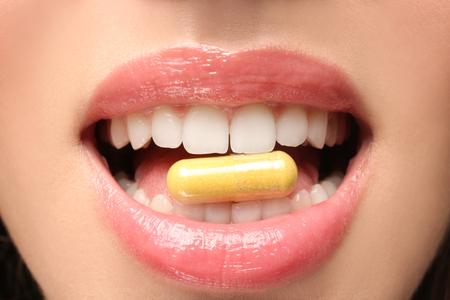 Giovane donna che prende pillola, primo piano. Concetto di perdita di peso