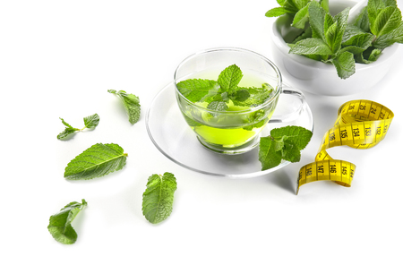 Composition with herbal tea, mint leaves and measuring tape on white background. Weight loss concept 免版税图像