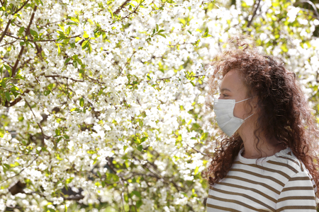 Young girl wearing protective mask among blooming trees in park Stock Photo