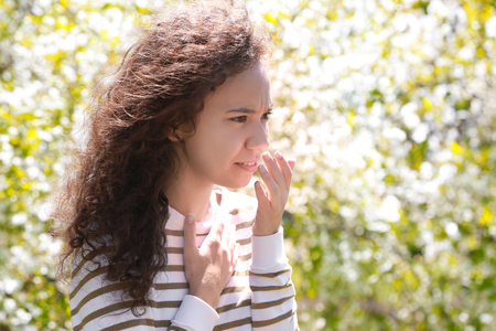 Allergy concept. Young woman suffering from cough among blooming trees in park