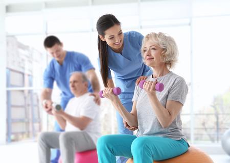 Fisioterapisti che lavorano con pazienti anziani in clinica moderna
