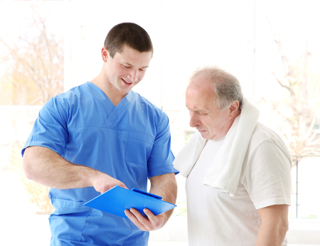 Physiotherapist with elderly patient in modern clinic