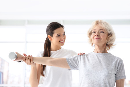 Physiotherapist working with elderly patient in modern clinic Stock Photo