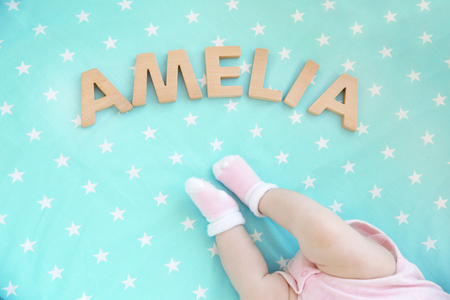 Legs of cute baby and word AMELIA composed of wooden letters on bed. Choosing name concept