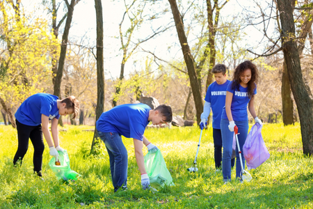 Gruppo di giovani volontari nel parco in giornata di sole Archivio Fotografico