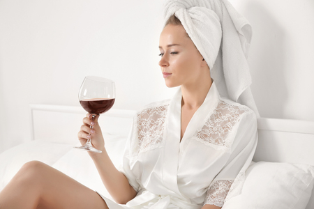Beautiful young woman in bathrobe after shower with glass of red wine on bed Stock Photo