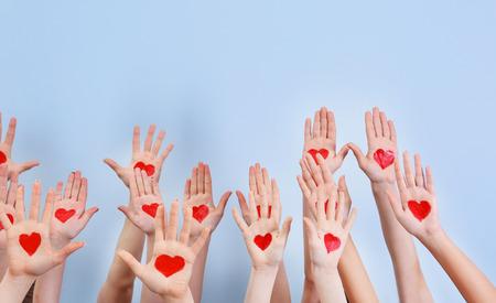 Alzato in aria le mani con cuori disegnati sui palmi contro uno sfondo chiaro. Concetto di volontariato