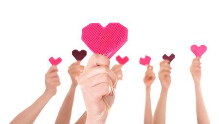 Les gens mettent les mains en l'air avec de petits coeurs sur fond blanc. Notion de volontariat