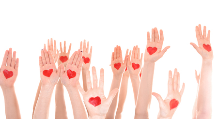 Raised in air hands with drawn hearts on palms against white background. Volunteering concept Foto de archivo