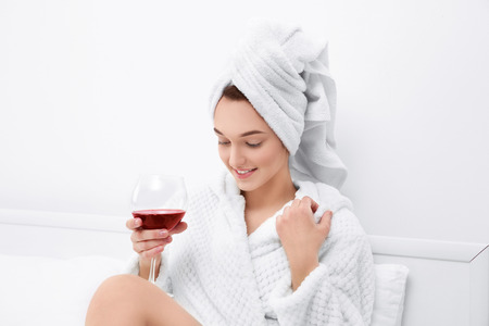 Beautiful young woman after shower in bathrobe with glass of red wine at home Stock Photo