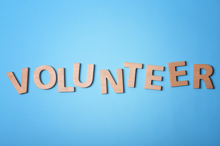 Word VOLUNTEER made of wooden letters on color background Stock Photo
