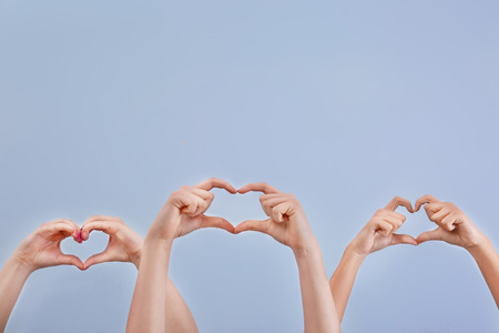 Hearts made by raised hands on light background. Volunteering concept 免版税图像