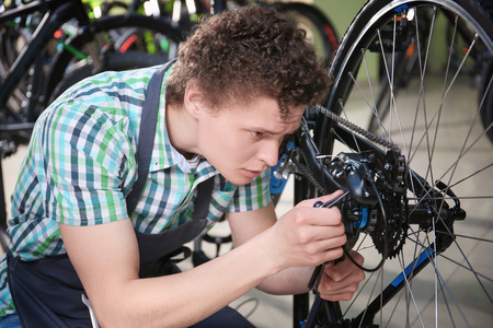 Young man checking bicycle in repair shop Stock fotó