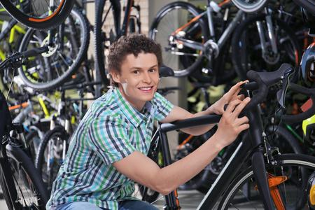 Young man choosing bicycle in shop