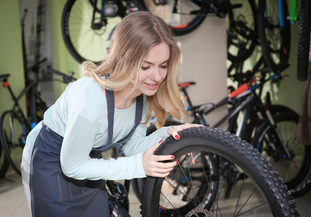 Young woman checking bicycle wheel in repair shop