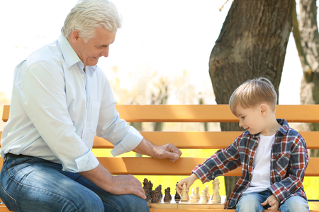 Cute little boy with his grandfather playing chess on bench in spring park
