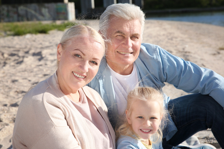 Happy grandparents with little girl sitting on river bank Stock Photo