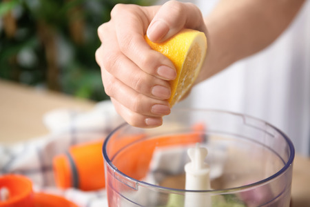Woman squeezing lemon juice into blender bowl for preparing yogurt sauce in kitchen