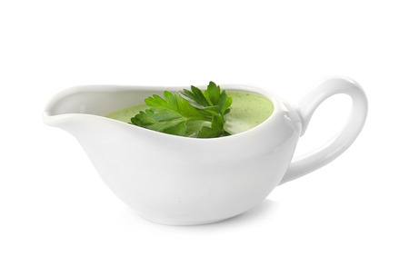 Delicious yogurt sauce with parsley leaves in gravy boat isolated on white