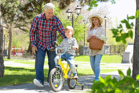 Cute little boy riding on bicycle and his grandparents in spring park