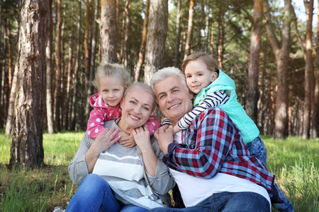 Happy grandparents with little children sitting on grass in forest 写真素材