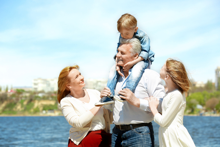 Cute happy children with grandparents walking on embankment