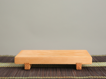 Wooden board on bamboo mat against grey background