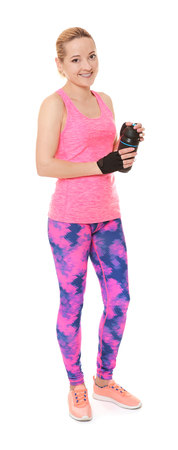 Young sporty woman with beverage on white background 免版税图像