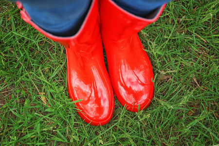Young woman in red rubber boots on green grass Stock Photo