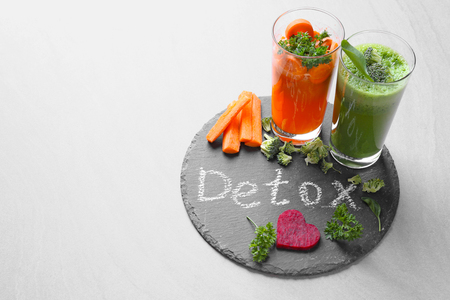 Fresh juices in glasses and ingredients on slate plate with word DETOX