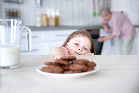 Cute little girl taking chocolate cookies from plate and blurred grandmother on background Stock Photo - 111238724