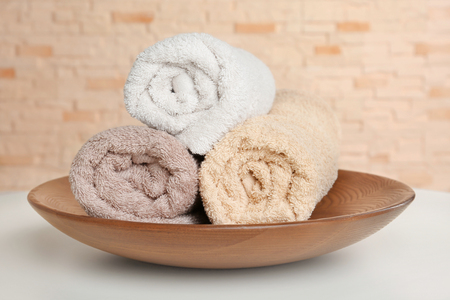 Plate with soft rolled towels and on table Stock Photo